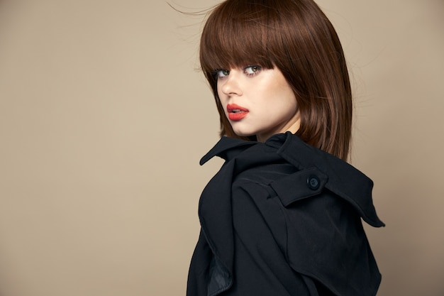 Modelo bonito casaco escuro de bom humor sorrindo em um retrato de fundo bege