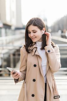 Modelo bonito colocar seus fones de ouvido sem fio durante a chamada de vídeo