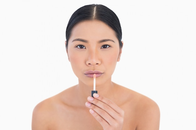 Modelo bonito e concentrado aplicando brilho labial