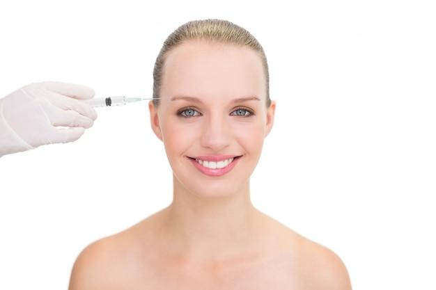 Modelo bonito e loiro bonito que recebe a injeção de botox