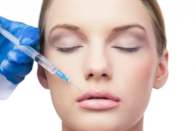 Modelo bonito e pacífico com injeção de botox acima dos lábios
