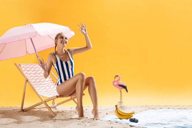 Modelo bonito em roupas de praia posa acenando a mão e sorrindo