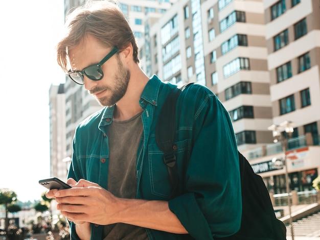 Modelo bonito hippie elegante confiante. homem vestido de camiseta. homem de moda posando na rua perto de uma parede branca. mensagens de texto em seu celular. escreve sms no smartphone