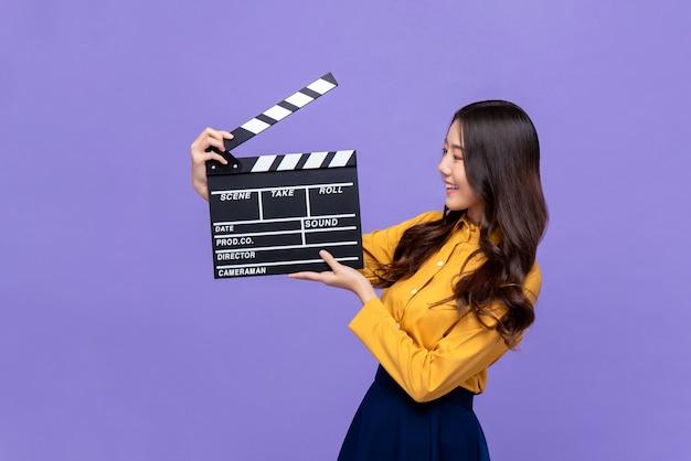 Modelo bonito jovem mulher asiática segurando claquete de cinema