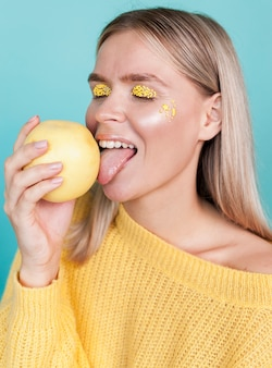 Modelo bonito lambendo frutas studio shot