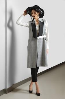 Modelo bonito na jaqueta sem mangas, calça, camisa e chapéu de aba larga com flores