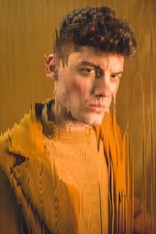 Modelo bonito olhando para a câmera por trás do vidro molhado