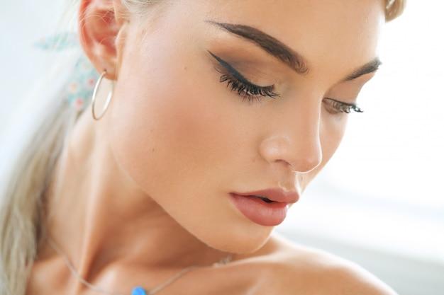 Modelo bronzeado com maquiagem esfumaçada nos olhos, olhando para baixo
