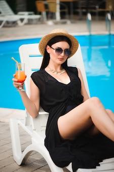 Modelo bronzeado jovem com roupa de verão elegante, aproveitando a festa na piscina, segurando um cocktail saboroso álcool.