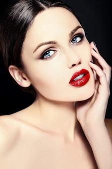 Modelo caucasiano jovem com maquiagem brilhante, pele limpa perfeita e lábios vermelhos coloridos