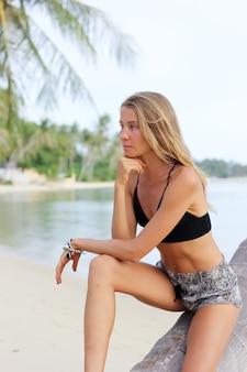 Modelo caucasiano magro e bronzeado em uma palmeira em uma praia tropical