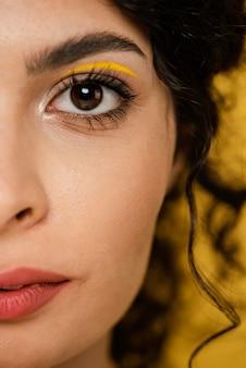 Modelo close-up com maquiagem amarela