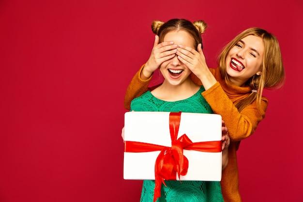 Modelo cobrindo os olhos de sua amiga e dando-lhe grande caixa de presente
