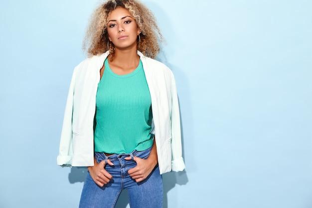 Modelo colocando sua jaqueta branca. mulher posando em roupas casuais modernas