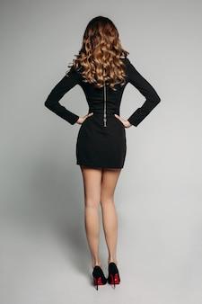 Modelo com brilhantes cabelos ondulados em mini vestido preto e sapatos de salto altos com as mãos na cintura.