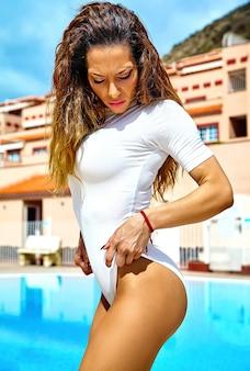 Modelo com cabelo escuro em trajes de banho branco saindo da piscina