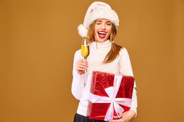 Modelo com chapéu de papai noel e caixa grande de presente bebendo champanhe na parede dourada