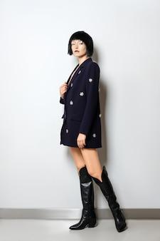 Modelo com corte de cabelo preto bob posando perto da parede de jaqueta azul com decoração de pedras preciosas e em botas altas largas