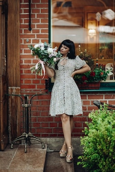 Modelo com flores em pé no degrau de um restaurante