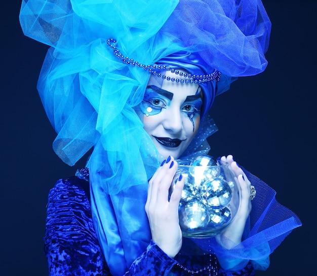 Modelo com maquiagem azul e roupa segurando guirlanda de luz