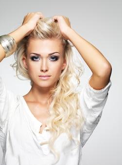 Modelo com maquiagem brilhante. retrato de uma jovem mulher fashion com longos cabelos loiros