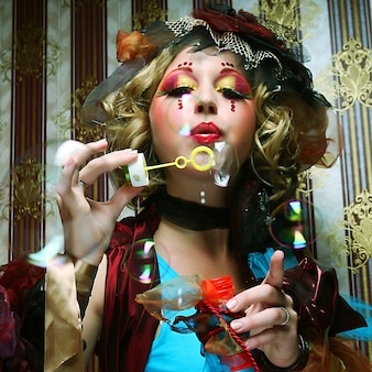 Modelo com maquiagem criativa soprando bolhas de sabão.