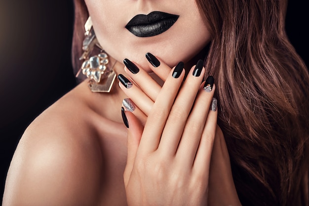 Modelo com maquiagem escura, cabelos compridos e preto