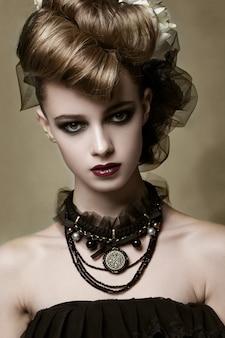 Modelo com maquiagem gótica e jóias pretas e penteado de halloween sobre fundo verde