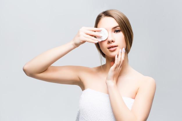 Modelo com maquiagem natural limpa o rosto com uma esponja branca no olho.