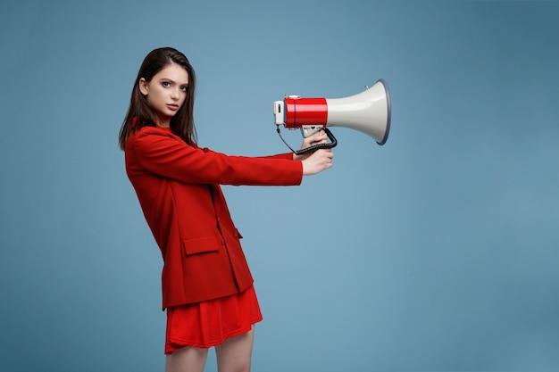 Modelo com megafone em uma saia de paletó vermelho. mulher jovem e bonita com fundo azul