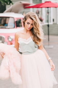 Modelo com saia de tule em fundo de carro retrô. ela tem longos cabelos loiros, segura um casaco de pele rosa na mão, olhando para baixo.