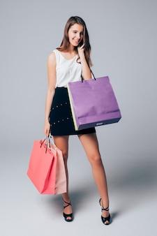 Modelo com sapatos de salto alto segura diferentes sacos de papel de compras isolados no branco