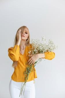 Modelo com uma blusa amarela com flores delicadas em um fundo cinza com maquiagem de outono