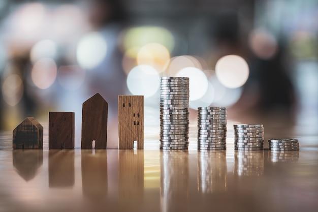 Modelo da casa de madeira e fileira do dinheiro da moeda no fundo branco, mercado imobiliário