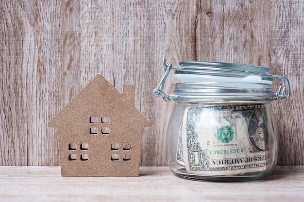 Modelo da casa de madeira e frasco de vidro do dinheiro, nota de dólar americano.