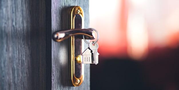 Modelo da casa e chave na porta da casa. imobiliária oferece casa