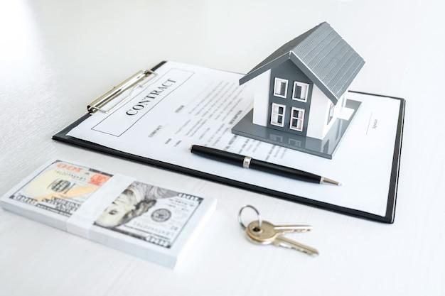 Modelo da casa e dinheiro, chave da casa no contrato imobiliário
