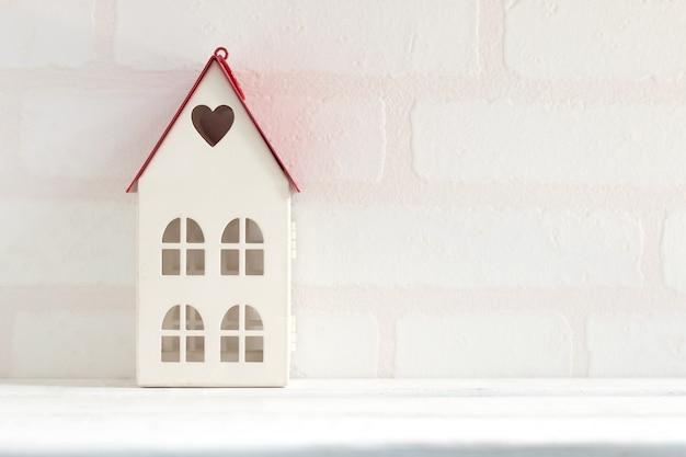 Modelo da casa no fundo de madeira branco do papel de parede do tijolo da tabela. conceito de negócio em casa.