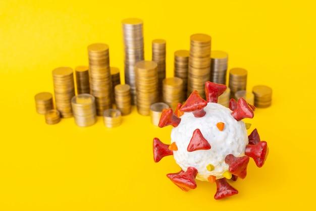 Modelo da célula covid-19 e pilhas de moedas no amarelo