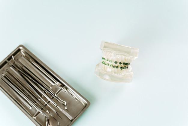 Modelo da mandíbula com aparelho em um fundo azul ao lado de instrumentos dentários