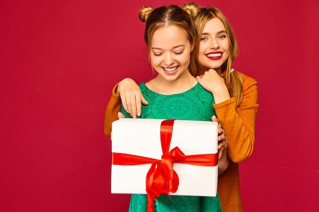 Modelo dando a sua amiga grande caixa de presente