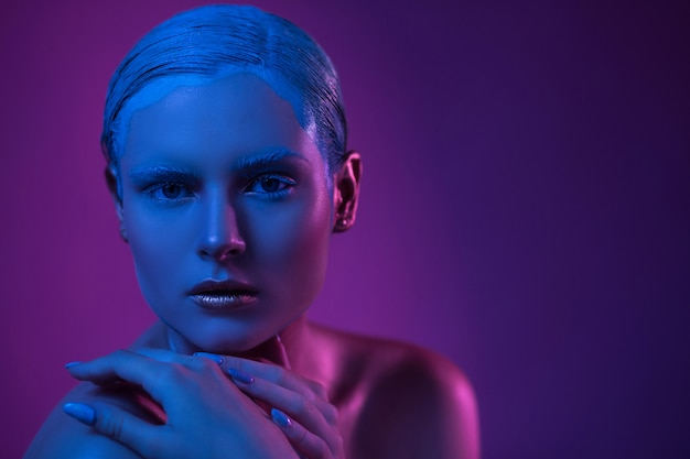 Modelo de alta moda em iluminação neon com maquiagem glitter