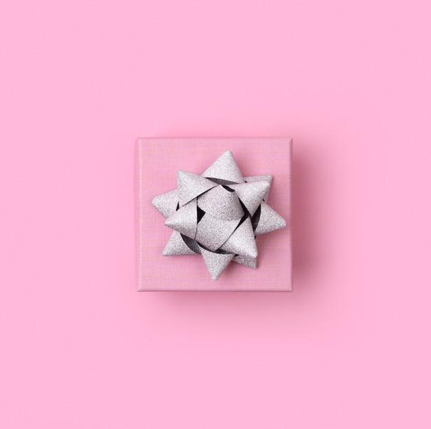 Modelo de aniversário de ano novo de natal. caixa de presente bonita sobre fundo de papel rosa pastel.