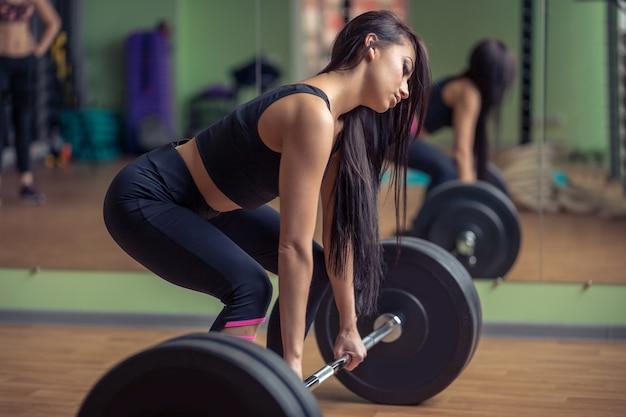 Modelo de aptidão feminina atlético segurando barra pesada e se preparando para o levantamento terra.