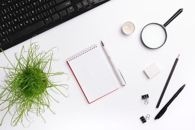 Modelo de área de trabalho de mesa de escritório em casa com teclado preto, notebook, vela, caneta, planta e outros acessórios de escritório.