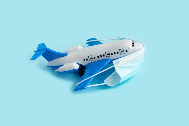 Modelo de avião com máscara médica protetora em azul