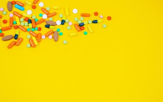 Modelo de avião com pílulas multicoloridas de close-up de enjoo em um fundo amarelo. conceito de doença em viagens. foco seletivo
