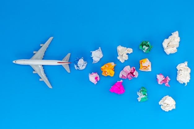 Modelo de avião com vários bola de papel em fundo azul com espaço de cópia