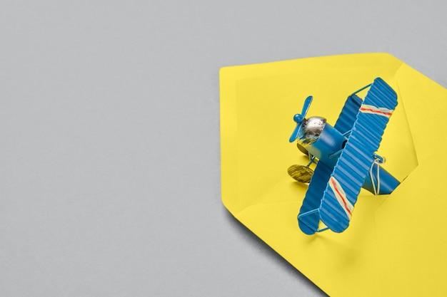 Modelo de avião de metal vintage e concerto amarelo na superfície cinza