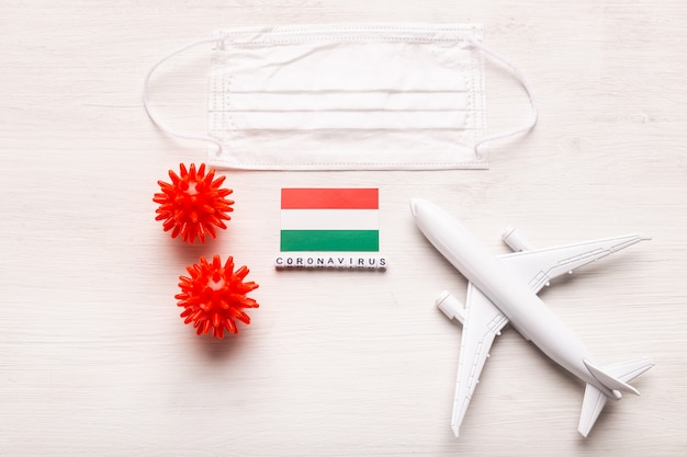 Modelo de avião e máscara facial e bandeira hungria. pandemia do coronavírus. proibição de voos e fronteiras fechadas para turistas e viajantes com coronavírus covid-19 da europa e ásia.